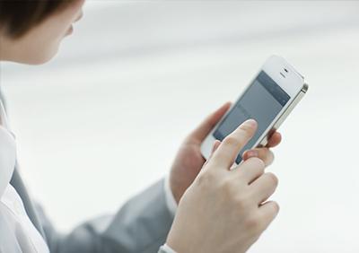 スマートフォンで履歴書を作成する女性の写真
